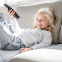 Little girl with remote lounging