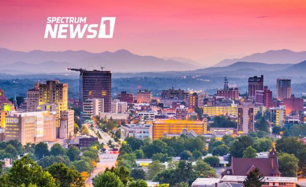 Spectrum News - City of Asheville skyline at dusk with mountains in background