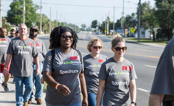 Happy volunteers walk to a home
